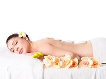 Frau, die im Badekurortsalon mit heißen Steinen sich entspannt Stockbilder