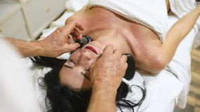 Frau, die im Badekurortsalon mit heißen Steinen sich entspannt stock video