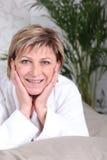 Frau, die im Bademantel lächelt Lizenzfreie Stockfotos