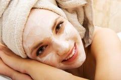Frau, die im Badezimmer mit Gesichtsmaske sich entspannt Stockbilder