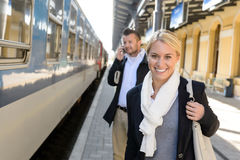 Frau, die im Bahnstationmanntelefon lächelt Stockfoto
