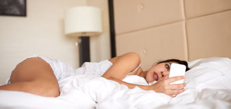 Frau, die im Bett betrachtet Handy liegt stockfotografie