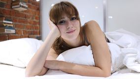 Frau, die im Bett blickt in Richtung Camerea sich entspannt Lizenzfreie Stockbilder
