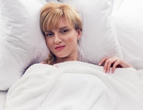 Frau, die im Bett lächelt Stockfotografie