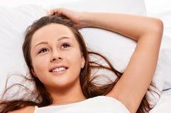 Frau, die im Bett lächelt Stockbilder