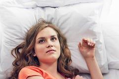 Frau, die im Bett lächelt Lizenzfreie Stockfotografie