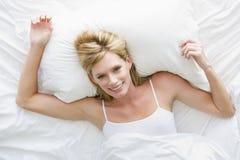 Frau, die im Bett liegt Lizenzfreie Stockfotografie