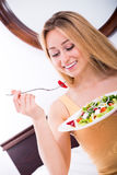 Frau, die im Bett liegt und Salat isst Lizenzfreies Stockbild