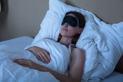 Frau, die im Bett mit Augenmaske schläft stockbild