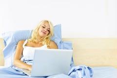 Frau, die im Bett mit Computer sitzt Lizenzfreies Stockfoto
