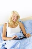 Frau, die im Bett mit Tabletteeinheit sitzt Stockfotografie