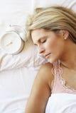 Frau, die im Bett mit Wecker schläft lizenzfreies stockfoto