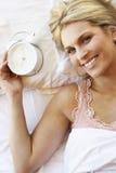Frau, die im Bett mit Wecker sich entspannt lizenzfreie stockfotografie
