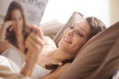 Frau, die im Bett mit Zeitschrift sich entspannt Lizenzfreies Stockbild