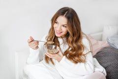 Frau, die im Bett morgens frühstückt Lizenzfreies Stockfoto