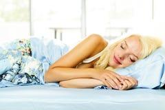 Frau, die im Bett schläft Lizenzfreie Stockfotos