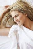Frau, die im Bett sich entspannt stockfoto