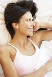 Frau, die im Bett sich entspannt lizenzfreie stockfotografie