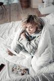 Frau, die im Bett sitzt und nach Auseinanderbrechen sentimental sich fühlt lizenzfreie stockfotografie