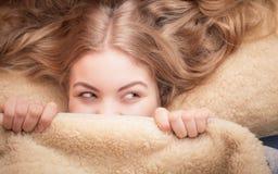 Frau, die im Bett unter Decke liegt Stockbild
