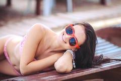 Frau, die im Bikini am tropischen Reiseerholungsort ein Sonnenbad nimmt. Schöne junge Frau, die auf Sonnenruhesessel nahe Pool lie Lizenzfreie Stockfotografie