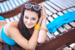 Frau, die im Bikini am tropischen Reiseerholungsort ein Sonnenbad nimmt. Schöne junge Frau, die auf Sonnenruhesessel nahe Pool lie Stockfotos