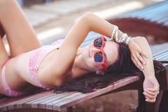 Frau, die im Bikini am tropischen Reiseerholungsort ein Sonnenbad nimmt. Schöne junge Frau, die auf Sonnenruhesessel nahe Pool lie Stockbild
