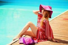 Frau, die im Bikini am tropischen Reiseerholungsort ein Sonnenbad nimmt. Schöne junge Frau, die auf Sonnenruhesessel nahe Pool lie Lizenzfreie Stockfotos