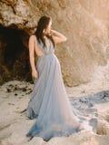 Frau, die im blauen Hochzeitskleid im Strand an den Sonnenuntergang- oder Sonnenaufgangfarben aufwirft Blonde Frau des Art und We Lizenzfreies Stockbild
