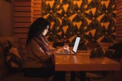 Frau, die im Café mit Laptop sitzt stockfoto