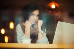 Frau, die im Café sitzen und Lächeln eingewickelt im Schal lizenzfreies stockfoto