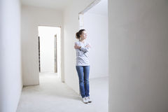 Frau, die im Eingang der neuen Wohnung sich lehnt stockfoto