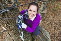 Frau, die im Erlebnispark klettert Lizenzfreie Stockbilder