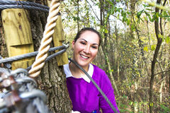 Frau, die im Erlebnispark klettert lizenzfreie stockfotos