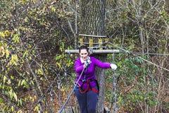 Frau, die im Erlebnispark klettert stockfotos