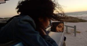 Frau, die im Flügelspiegel des Kleintransporters Strand 4k betrachtet stock footage