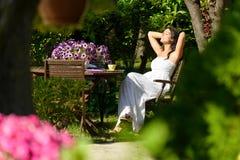 Frau, die im Garten auf Sommer stillsteht Stockbild