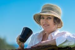 Frau, die im Garten mit Tasse Kaffee sitzt Stockbild