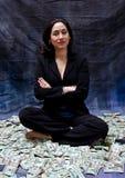 Frau, die im Geld sitzt lizenzfreie stockfotos