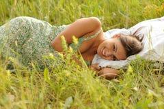 Frau, die im Gras liegt Lizenzfreie Stockfotos