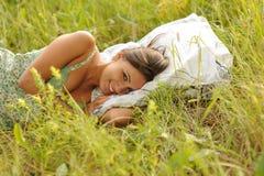 Frau, die im Gras liegt Lizenzfreie Stockbilder