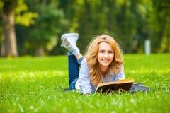 Frau, die im Gras liegt und ein Buch liest Lizenzfreie Stockfotos