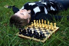 Frau, die im Gras nahe dem Schachvorstand liegt Lizenzfreie Stockbilder