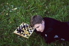 Frau, die im Gras nahe dem Schachvorstand liegt Stockfoto