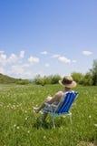 Frau, die im Gras sich entspannt Stockfotografie