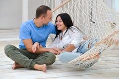 Frau, die im Hängemattenlächeln und im Mannsitzen sich entspannt Stockbilder