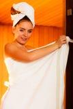 Frau, die im hölzernen Saunaraum sich entspannt Lizenzfreie Stockbilder