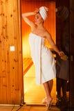 Frau, die im hölzernen Saunaraum sich entspannt Lizenzfreies Stockbild