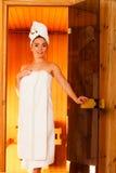 Frau, die im hölzernen Saunaraum sich entspannt Stockfotografie