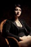 Frau, die im hölzernen Stuhl sitzt Lizenzfreies Stockfoto